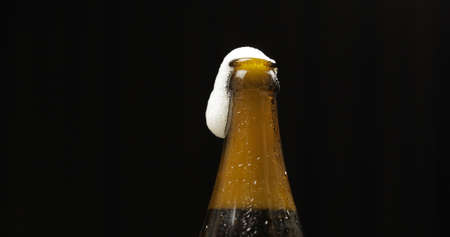 Opened cold bottle of beer. Cold beer on a black background. Craft beer in bottle with condensate and water drops. Close-up shot 免版税图像