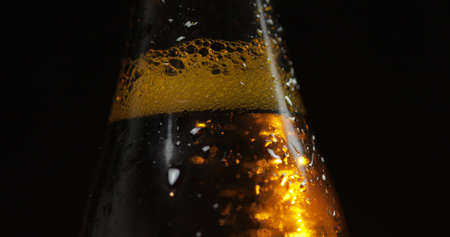 A bottle of cold beer on a black background. A ray of light beautifully illuminates it. Craft light beer in bottle with condensate and water drops