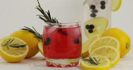 Cold drink in drinking glass. Refreshing soda lemonade red cocktail with lemon, ice cubes and black currant in a glass. Tonic fizzy water with bubbles. White background