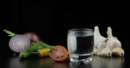 Shot of vodka in glass with onion, hot pepper, cherry tomato, dill and garlic against black background 免版税图像