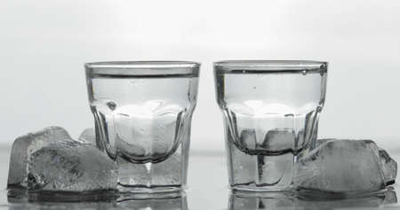 Shots of vodka in glasses. White background with ice cubes. Alcohol drink vodka tequila