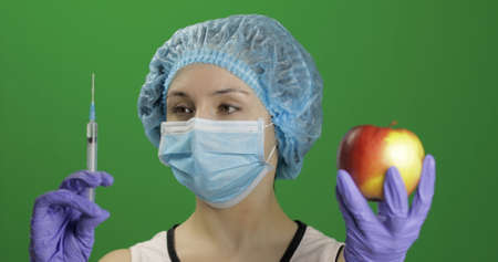 Female scientist holding syringe with medicines in one hand and an apple in other hand. She chooses syringe with medicines. Concept of medicine method of treatment. Chroma key background Stockfoto