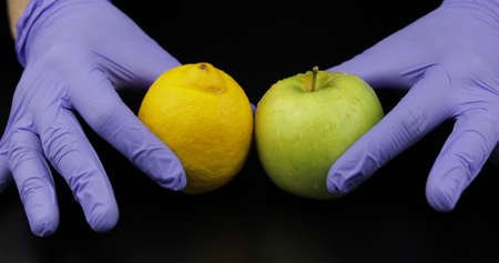 Doctors hands with apple and lemon on black background. Concept healthy life without pills, drugs. To be healthy from fruit vitamins