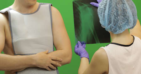 Man with shoulder injury. Wearing a bandage for fixing of an elbow joint and a humeral belt. Dislocations of arm of the forearm, shoulder. Broken bones. Nurse examines x-ray, gives advice to patient
