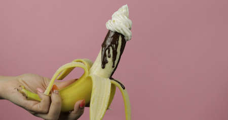 Banana with melted dark chocolate syrup and with whipped cream on top of the fruit. A peeled banana covered in chocolate cream. Pink background