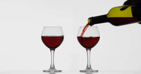 Wine. Red wine pouring in wine glass over white background. Rose wine pour from the bottle