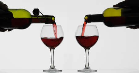 Wine. Red wine pouring in two wine glasses over white background. Rose wine, red juice pour into a glass. Close up shot