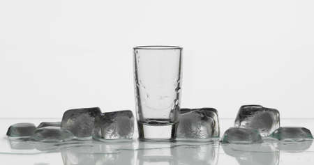 Empty shot glass of vodka with ice cubes. White background. Close-up shot