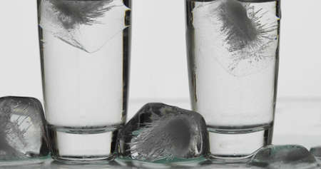 Two shots of vodka in glasses with ice cubes. White background. Alcohol drink vodka tequila. Close-up shot