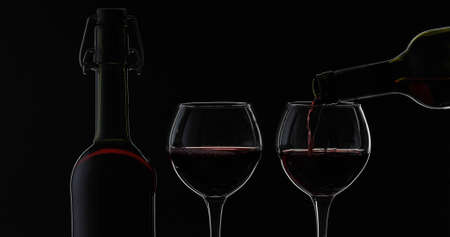 Wine. Red wine pouring in wine glass over black background. Rose wine pour from the bottle. Silhouette. Close up shot