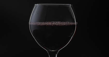Rose wine. Red wine in wine glass over black background. Silhouette. Close up shot