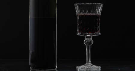 Rose wine. Red wine in wine glass with bottle over black background. Silhouette. Close up shot