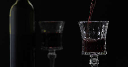 Wine. Red wine pouring in wine glass over black background. Rose wine pour. Silhouette. Close up shot Stok Fotoğraf