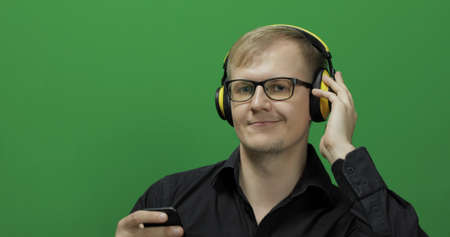 Guy listens to music in wireless yellow headphones. Portrait of attractive man using smart phone for listening the music in headphone while sitting near green screen. Chroma key Фото со стока