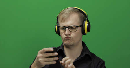Guy using smart phone in wireless yellow headphones. Portrait of attractive man using mobile phone in headphone while sitting near green screen. Chroma key