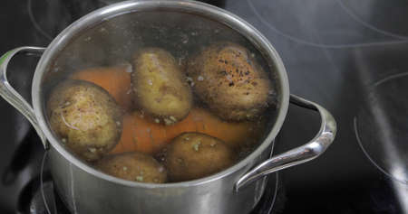 Hot boiling pan with vegetables potatoes and carrots. Cooking in a pan on the home kitchen Stock Photo