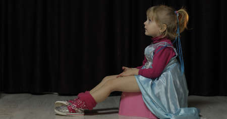 Little girl sitting on the potty and watching TV. Blonde cute child in blue dress. Inside