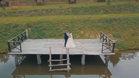 Groom with bride near lake in the park. Wedding couple. Man and woman in love. Aerial shot Stock Photo