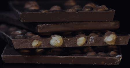 Dark chocolate blocks with nuts details slow close-up macro. Chocolate bars. 版權商用圖片