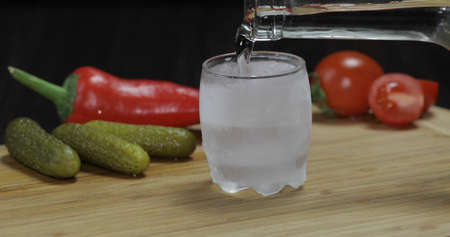 Pour vodka from a bottle into icy shot glass. Cherry tomatoes, marinated cucumbers, pepper on the table.