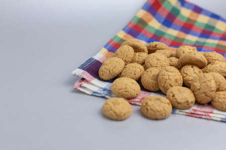Pepernoten, a traditional treat with the Dutch holiday Sinterklaas. Kruidnoten, pepernoten, traditional cookie sweets, strooigoed on colorful towel. St. Nicolas day concept Stock Photo