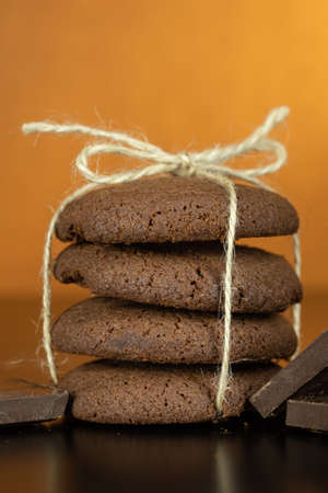 Tasty looking chocolate cookie on dark surface. Vintage warm background.