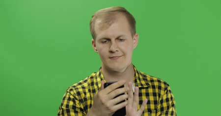 Caucasian fashionable man scrolling or texting on the smartphone in his hands. Chroma key