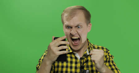Caucasian fashionable man scrolling or texting on the smartphone in his hands. Guy very emotionally celebrates something doing yes gesture with his hand in front of the camera. Chroma key