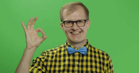 Caucasian happy man in glasses showing OK gesture. Guy in yellow shirt. Green screen. Chroma key