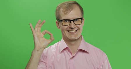 Caucasian man in glasses showing OK gesture. Guy in pink shirt. Green screen. Chroma key