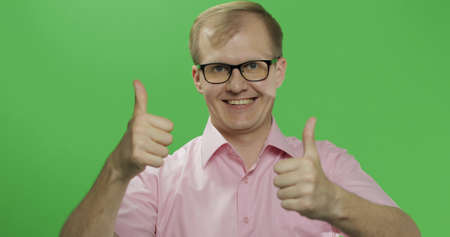 Caucasian man in glasses show thumbs up. Guy in pink shirt. Green screen. Chroma key Imagens