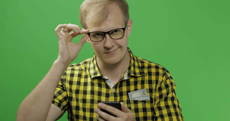 Caucasian man in glasses scrolling or texting on the smartphone in his hands and smiling. Green screen. Chroma key Imagens