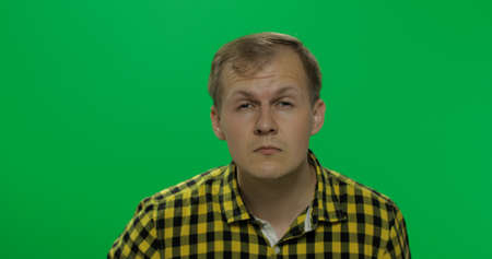 Handsome young man in the yellow shirt without glasses sees poorly on the chroma key background. Poor eyesight concept. Green screen.