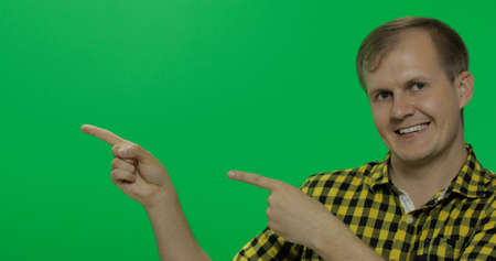 Caucasian man in eyeglasses showing something. Guy in yellow shirt. Place for your logo or text. Green screen. Chroma key