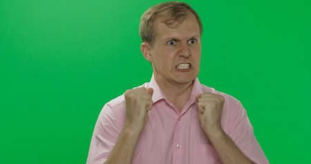 Angry aggressive handsome young man in pink shirt nervous and can not hold back emotions over a green screen background. Chroma key Stock fotó