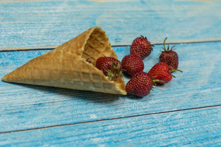 Berry season. Berry ice cream. Berries of strawberry in a waffle on a blue wooden background