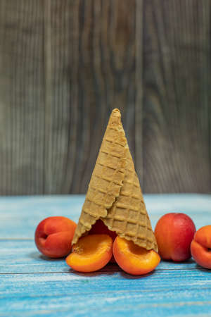 Fruit ice cream. Flat lay fresh apricotin a waffle cone on wooden background. Summer sweet menu concept. Homemade ice cream making Banque d'images - 124741810