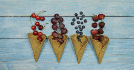 Berry and fruit ice cream. Flat lay various fresh fruits blueberry, strawberry, cherry, grape in a waffle cone on blue wooden background. Summer sweet menu concept. Homemade ice cream making Banque d'images - 124741812