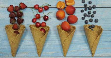 Berry and fruit ice cream. Flat lay various fresh fruits blueberry, strawberry, cherry, apricot in a waffle cone on blue wooden background. Summer sweet menu concept. Homemade ice cream making Banque d'images - 124741822
