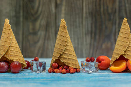 Berry and fruit ice cream. Flat lay various fresh fruits apricot, strawberry, grape in a waffle cone on wooden background. Summer sweet menu concept. Homemade ice cream making Banque d'images - 124741824