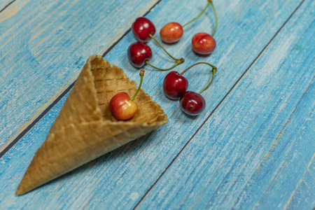Berry season. Berry ice cream. Berries of cherry in a waffle on a blue wooden background Banque d'images - 124741827