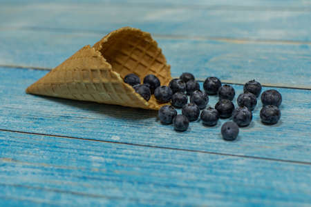 Berry season. Berry ice cream. Berries of blueberries in a waffle on a blue wooden background Banque d'images - 124741832