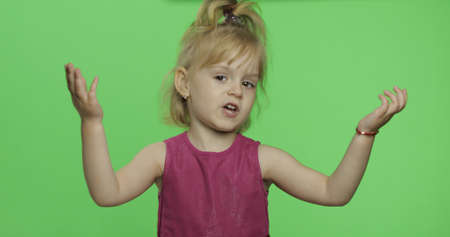 Positive girl talking with expression in purple dress. Happy four years old girl. Pretty little child, 3-4 year old blonde girl. Make faces and smile. Green screen. Chroma Key
