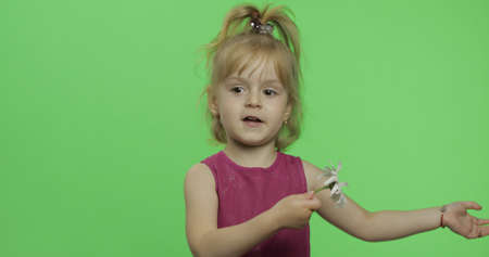 Positive girl in purple dress holds chamomile flower. Pretty little blonde child. Make faces. Place for your logo or text. Green screen. Chroma Key