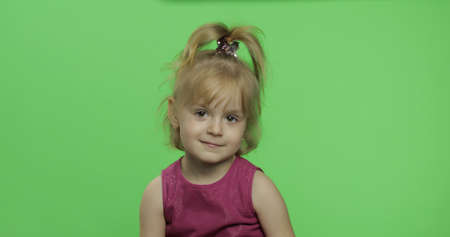 Positive girl looking to a camera in purple dress. Happy four years old girl. Pretty little blonde child. Make faces and smile. Place for your logo or text. Green screen. Chroma Key Archivio Fotografico