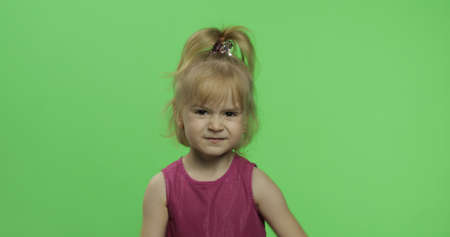 Disappointed girl in purple dress. Pretty little blonde child. Make faces. Place for your logo or text. Green screen. Chroma Key