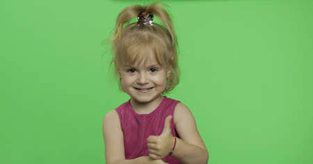 Positive girl looking to a camera in purple dress. Thumbs up. Happy four years old girl. Pretty little blonde child. Make faces and smile. Place for your logo or text. Green screen. Chroma Key