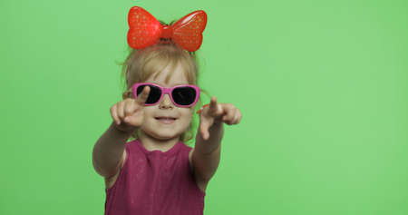 Positive girl in purple dress, sunglasses and red ribbon on head shows a finger forward to camera. Pretty little blonde child. Make faces. Place for your logo or text. Green screen. Chroma Key