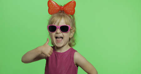 Positive girl in purple dress, sunglasses and red ribbon looking at camera. Thumbs up. Pretty little blonde child. Make faces. Place for your logo or text. Green screen. Chroma Key