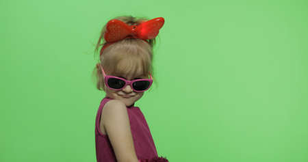 Positive girl in purple dress, sunglasses and red ribbon looking at camera. Pretty little blonde child. Make faces. Place for your logo or text. Green screen. Chroma Key